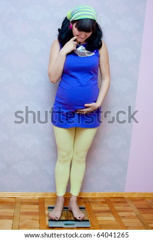pregnant woman standing on scales and holding her baby bump