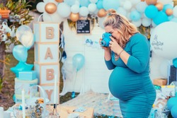 Pregnant woman taking photos of a decorated table for baby shower. Photocamera, party decorations in white and blue colors, baby boy