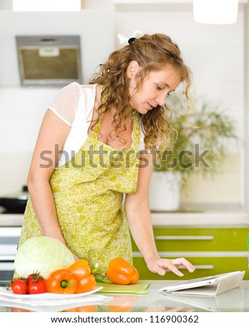 pregnant woman using a tablet computer to cook in her kitchen