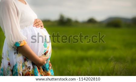 Pregnant woman wearing floral white dress affectionately holding her belly outside with newly planted rice field and cloudy sky in background.