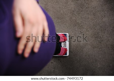 Pregnant woman weighing on scale