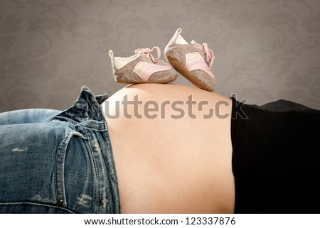 pregnant woman with a pair of shoes on her tommy