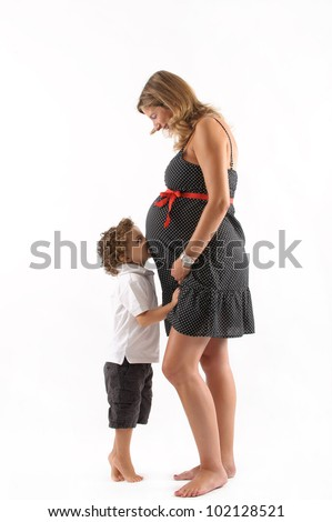 pregnant woman with a small kid kissing her belly