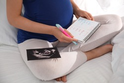 Pregnant woman with baby names list and sonogram sitting on bed, closeup