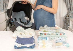 Pregnant woman with big tummy is packing baby clothes for going to maternity hospital. Pregnant bag for hospital. Concept of pregnancy preparation. Mother waiting baby.