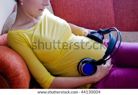 Pregnant woman with headphones on her belly lying on sofa