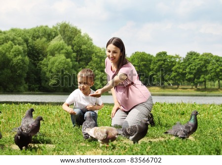 stock photo : Pregnant woman with her son feeding pigeons in a park