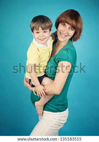 Pregnant woman with her son on blue background