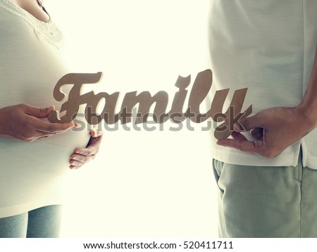 Pregnant woman with husband holding family message for incoming baby isolated on white background. Concept for baby shower and warm family.
