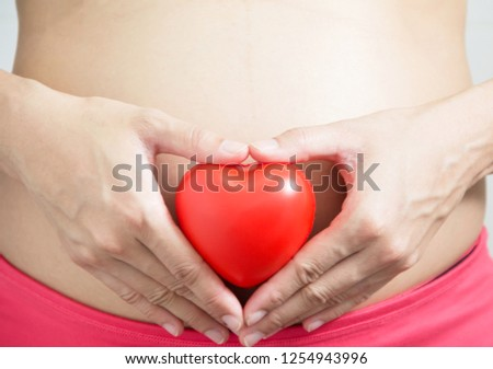 pregnant woman with red heart shape at the tummy, love and care concept #1254943996