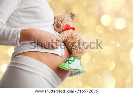 Pregnant woman with toy teddy bear. Young woman expecting a baby.