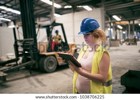 pregnant woman working in...