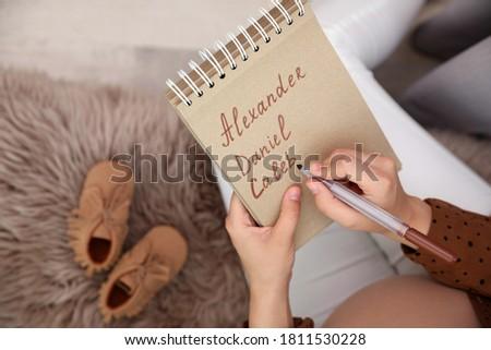 Pregnant woman writing baby names list, closeup Foto d'archivio ©