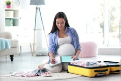 Pregnant woman writing packing list for maternity hospital at home