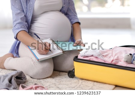 Pregnant woman writing packing list for maternity hospital at home, closeup