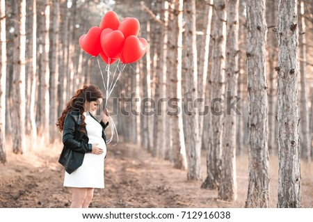 Pregnant woman 30-35 year old holding heart shape red balloons standing in forest. Wearing black leather jacket and white dress outdoors. Maternity. Motherhood.