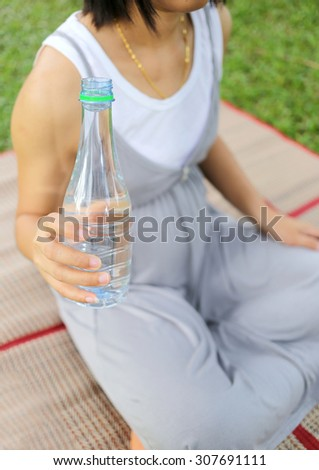 Pregnant women have a water bottle in hand to drink more water to the health of the baby.