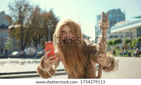 Prehistoric tribesman of neanderthals noticing somebody hurrying taking photographs like paparazzi on future smartphone in modern civilization city. Stock photo ©