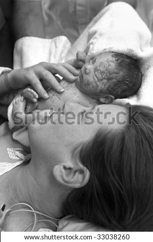 Premature baby boy delivered by Caesarean section, minutes after his birth, being shown to his Mother