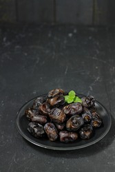 premium dates with a soft texture, in the photo on a black plate. with a dark background and potrait view foodphotography