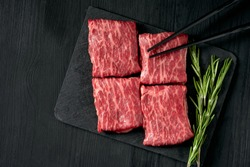 Premium raw Black Angus beef minute steak on Black wooden background. Slice wagyu for yakiniku