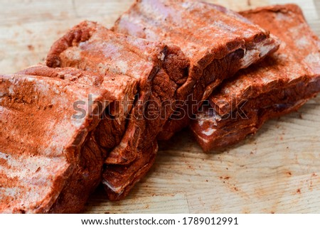 Premium raw pork ribs rubbed with red barbecue spices on a wooden plate, neutral background. Raw pork ribs ready to grill and smoke. Barbecue pork meat for grilling and smoking. Marinaded pork ribs