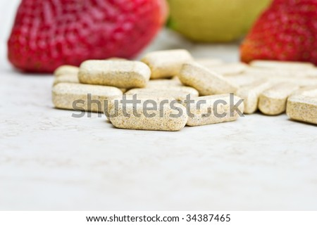 Prenatal vitamins with fresh fruit in the background. Shallow DOF with focus on front vitamin. - stock photo
