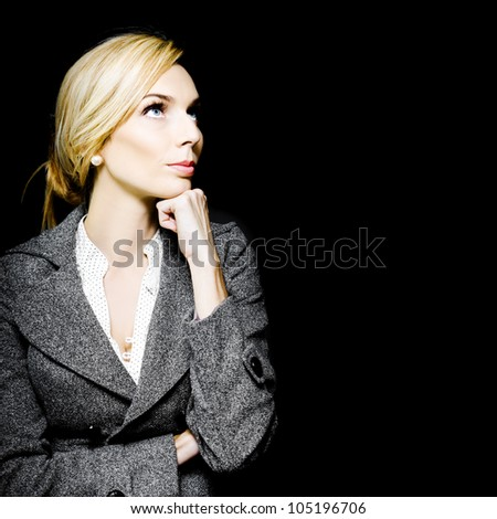Preoccupied beautiful business woman in an elegant vintage outfit deliberating her choices as she stares up towards copyspace with her chin resting on her hand