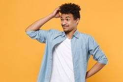 Preoccupied young african american guy in casual blue shirt posing isolated on yellow wall background studio portrait. People lifestyle concept. Mock up copy space. Put hand on head, looking aside