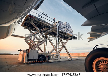 Preparation before flight. Loading of cargo containers to airplane at airport. Foto stock ©