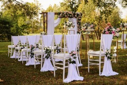 Preparation for a wedding ceremony outdoor in the park/ forest . Wood arch and chairs are decorated with white and pink flowers roses and peony, on the ground are many wood lanterns with candles.