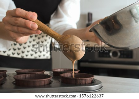 Preparation for baking a healthy chocolate fitness dessert of brownie or cupcakes without sugar.A female hand pours the dough into a baki. Wooden spoon