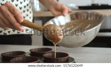 Preparation for baking a healthy chocolate fitness dessert of brownie or cupcakes without sugar.A female hand pours the dough into a baki