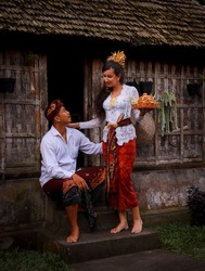 Preparation for Balinese ceremony. Multicultural couple preparing for Hindu religious ceremony with god's offerings. Bamboo house. Caucasian wife and Balinese husband. Penglipuran, Bali