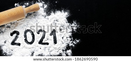 Photo of  Preparation for cooking home made cookie. Baking flour and 2021 on black board. Top view, flat lay with space for text. rolling pin, flour and shape of new year. New year ornament food background