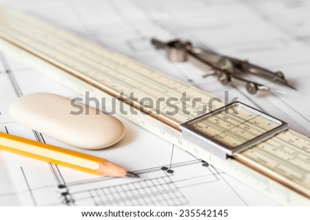 Preparation for drafting papers, the tools and schemes on the table. Angle view, focus on a compass