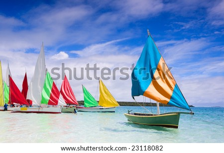 "Preparation for start of a sailing regatta in Mauritius. Colorful traditional Mauritian wooden boats called ""Pirogue""."