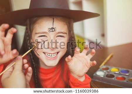 preparation for the celebration of Halloween. child in a witch outfit doing face painting. cute spider. idea of simple suit, diy, toned