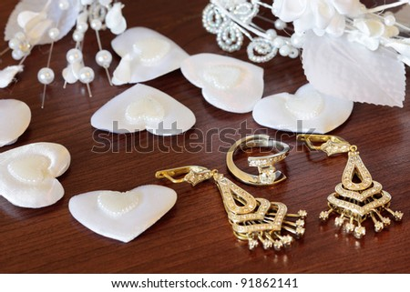 Preparation for the wedding, decoration of the bride, the ring, earrings, a diadem on a brown background
