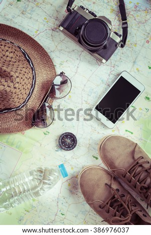 Preparation for travel,trip vacation, tourism mock up of cell phone,road ,compass,camera,hat,shoes,sunglasses on map. - Shutterstock ID 386976037