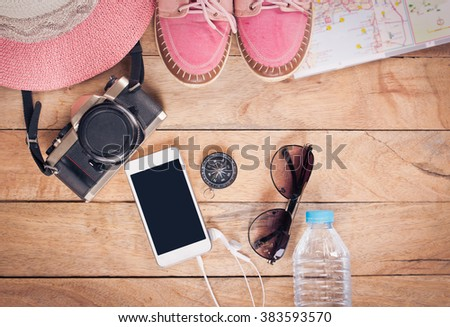 Preparation for travel,trip vacation, tourism mock up of cell phone,road map,compass,camera,hat,shoes on wooden table. #383593570