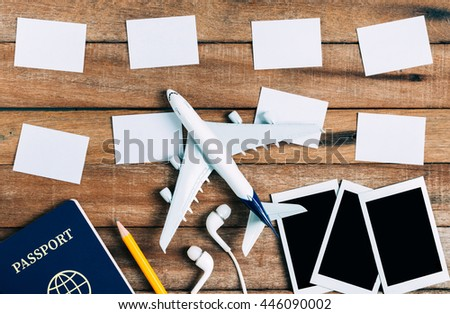 Preparation for Traveling concept and to do list, paper noted, airplane, photo frame, ear phone, pencil, passport on vintage wooden background.