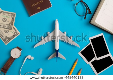 Preparation for Traveling concept, watch, airplane, money, passport, pencils, book, earphone, Photo frame, eyeglass  on blue background with copy space.