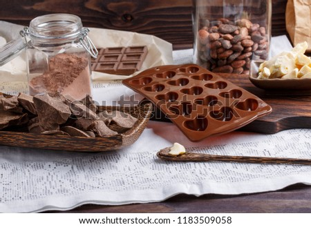 Preparation handmade chocolate candies. Ingredients for making chocolate - raw cocoa powder, cocoa mass, cocoa butter, cocoa beans.  Heart-shaped mold.