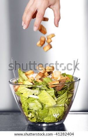 Preparation of a caesar salad in a glass bowl. Movement blur of crouton falling in the salad. Selective black and white with shallow depth of field.