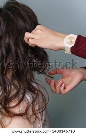 Preparation of bride. Hairstylist at work in process of creating hairstyles. Brown-haired person girl, side-view long hair, hairstyle collected, styling in beauty salon. Hand hairdresser straightens