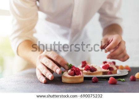 Photo of Preparation of cakes with raspberries on a table