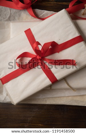 Preparation of christmas gifts. Present covered in white paper with red ribbon. Overhead view. #1191458500