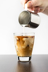 Preparation of cold brew iced coffee. Pouring milk into coffee shows the structure of a refreshing caffeine drink. Iced coffee latte with cream being poured