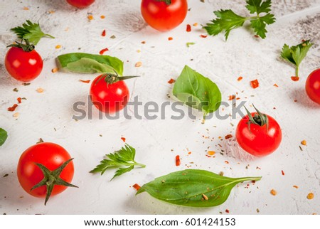 Preparation of food background: fresh tomatoes, basil leaves, parsley and seasoning, on a white concrete table, pattern #601424153